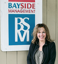 Photo of Yvette Perreca in front of Bayside Management sign.